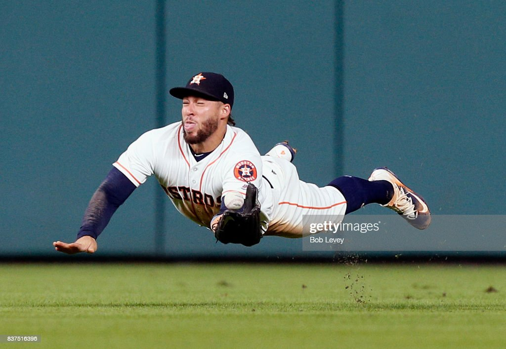 George Springer #4 of the Houston Astros comes up short on a diving attempt on a line drive by Michael Taylor #3 of the Washington Nationals in the fifth inning at Minute Maid Park on August 22, 2017 in Houston, Texas.