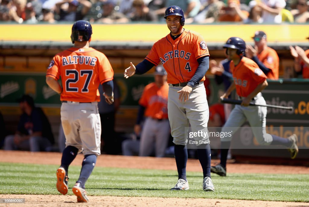 George Springer #4 of the Houston Astros congratulates Jose Altuve #27 after they both scored in the eighth inning against the Oakland Athletics at Oakland Alameda Coliseum on May 9, 2018 in Oakland, California.