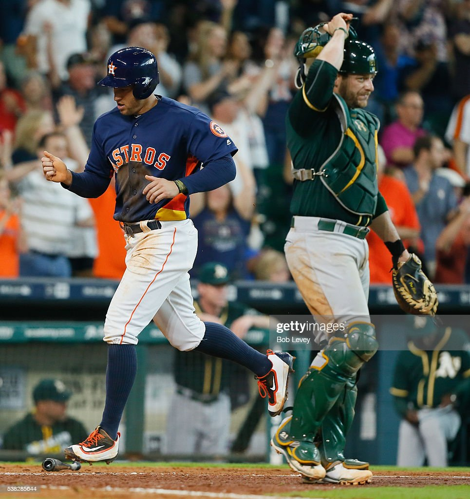 George Springer #4 of the Houston Astros crosses home plate in the seventh inning as Stephen Vogt #21 of the Oakland Athletics stands by at Minute Maid Park on June 5, 2016 in Houston, Texas.