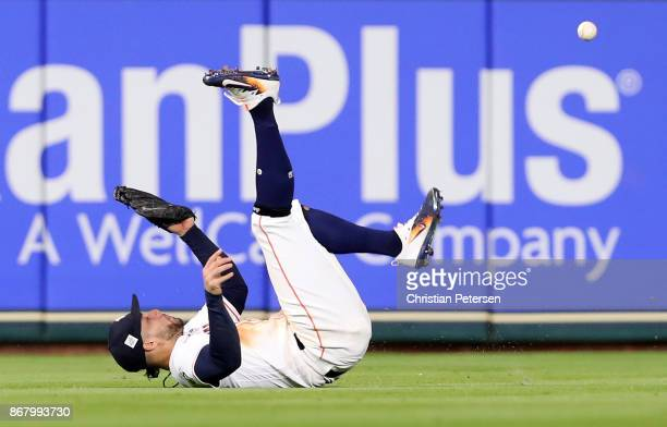 George Springer of the Houston Astros dives and fails to make a catch on a RBI triple by Cody Bellinger of the Los Angeles Dodgers during the seventh...