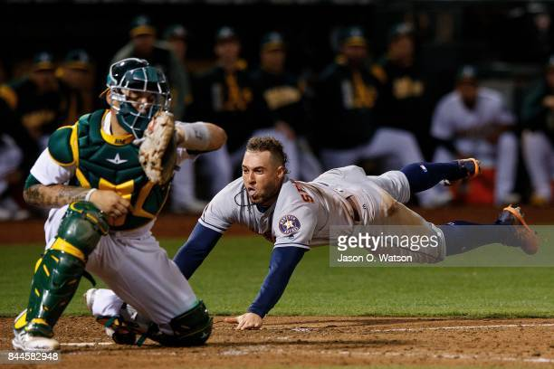 George Springer of the Houston Astros dives into home plate to score a run ahead of a tag from Bruce Maxwell of the Oakland Athletics during the...