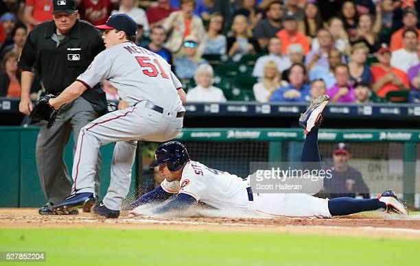 George Springer of the Houston Astros dives into home plate under the tag of Alex Meyer of the Minnesota Twins in the third inning of their game at...