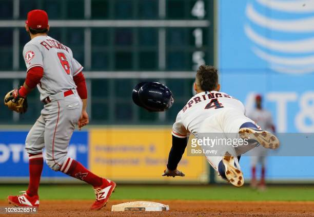 George Springer of the Houston Astros dives into second base with a double as David Fletcher of the Los Angeles Angels of Anaheim awaits the throw in...