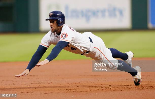 George Springer of the Houston Astros dives into third base in the first inning against the New York Yankees at Minute Maid Park on April 30, 2018 in...