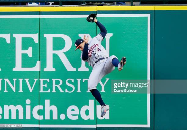 George Springer of the Houston Astros falls to the ground after catching a fly ball hit by Niko Goodrum of the Detroit Tigers during the first inning...