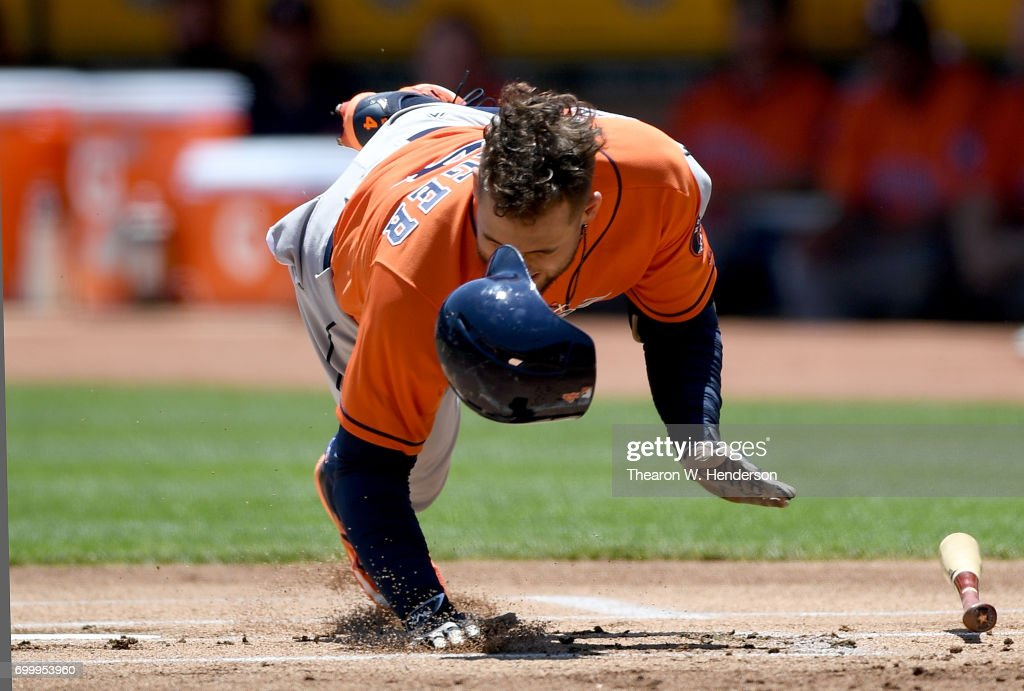 George Springer #4 of the Houston Astros falls to the ground after he was hit in the hand by a pitch from Jesse Hahn #32 of the Oakland Athletics in the top of the first inning at Oakland Alameda Coliseum on June 22, 2017 in Oakland, California.
