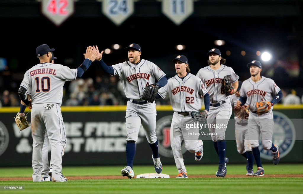 George Springer #4 of the Houston Astros greets Yuli Gurriel #10 as the team celebrates a win against the Seattle Mariners at Safeco Field on April 17, 2018 in Seattle, Washington. The Houston Astros won 4-1.