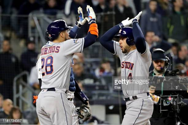 George Springer of the Houston Astros is congratulated by his teammate Robinson Chirinos after hitting a threerun home run against the New York...
