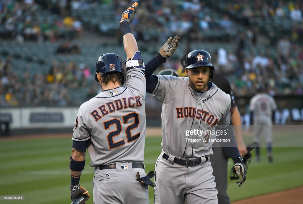 George Springer #4 of the Houston Astros is congratulated by Josh Reddick #22 after Springer hit a lead off home run against the Oakland Athletics in the top of the first inning at Oakland Alameda Coliseum on June 20, 2017 in Oakland, California.