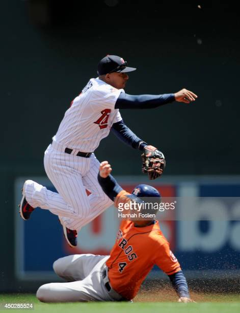 George Springer of the Houston Astros is out at second base as Eduardo Escobar of the Minnesota Twins turns a double play during the first inning of...