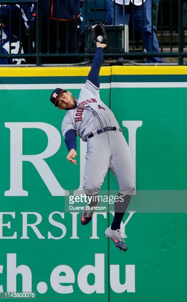 George Springer of the Houston Astros leaps up against the right field wall to catch a fly ball hit by Niko Goodrum of the Detroit Tigers during the...