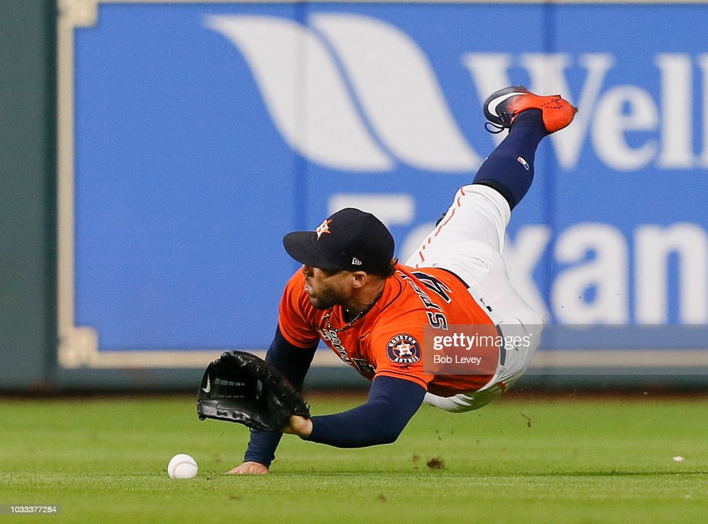 George Springer #4 of the Houston Astros makes a diving attempt on a soft line drive by A.J. Pollock #11 of the Arizona Diamondbacks in the eighth inning at Minute Maid Park on September 14, 2018 in Houston, Texas.