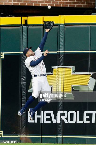 George Springer of the Houston Astros makes a leaoing attempt at a fly ball by Rougned Odor of the Texas Rangers but was unable to make the catch in...