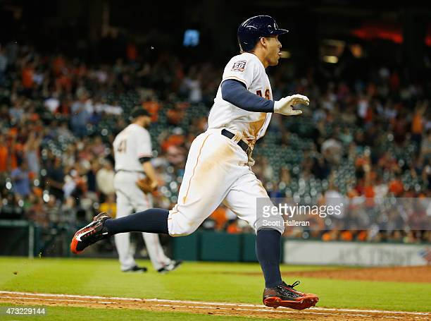 George Springer of the Houston Astros rounds first base after he hit a solo home run in the eighth inning off Jeremy Affeldt of the San Francisco...