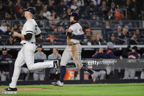 George Springer of the Houston Astros scores a run off of a wild pitch thrown by James Paxton of the New York Yankees during the first inning in game...