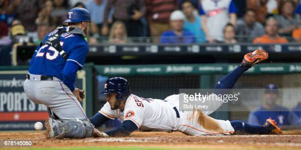 George Springer of the Houston Astros scores in the sixth inning on a sacrifice fly by Josh Reddick as Jonathan Lucroy of the Texas Rangers can't...