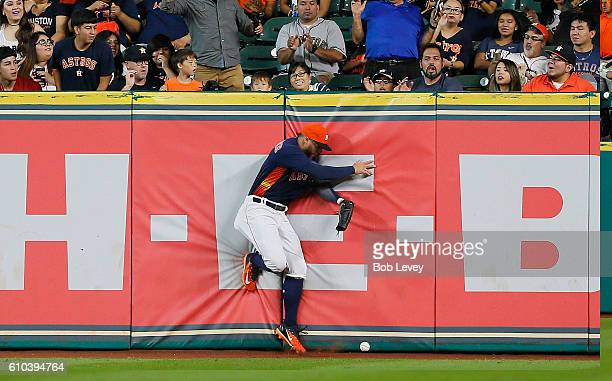 George Springer of the Houston Astros slams into the right field wall as he is unable to make the catch on a line drive by CJ Cron of the Los Angeles...