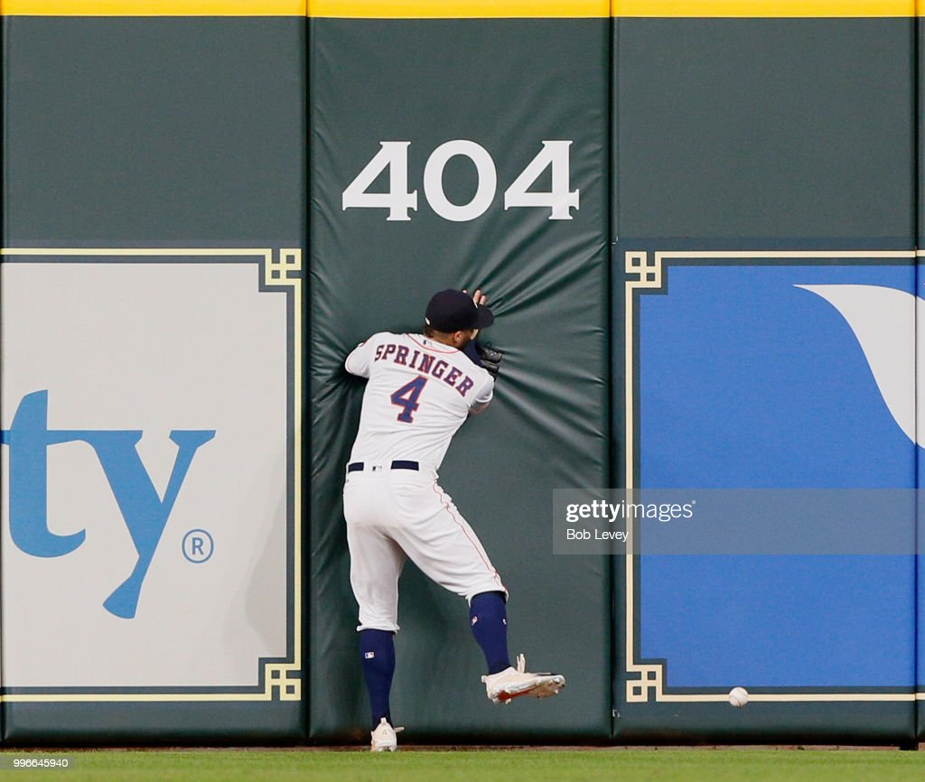 George Springer #4 of the Houston Astros slams into the wall as he attempts to catch a line drive from Khris Davis #2 of the Oakland Athletics in the sixth inning at Minute Maid Park on July 11, 2018 in Houston, Texas. Davis ended up with a triple.