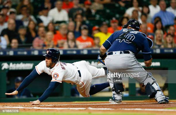 George Springer of the Houston Astros slides around Wilson Ramos of the Tampa Bay Rays in the first inning but missed home plate and was called out...