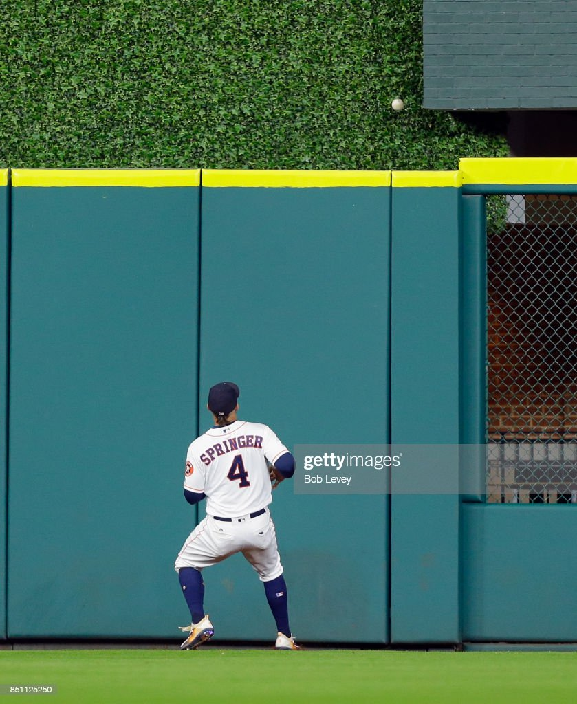 George Springer #4 of the Houston Astros watches a ball hit by Tim Anderson #7 of the Chicago White Sox go over the wall in the eighth inning at Minute Maid Park on September 21, 2017 in Houston, Texas.