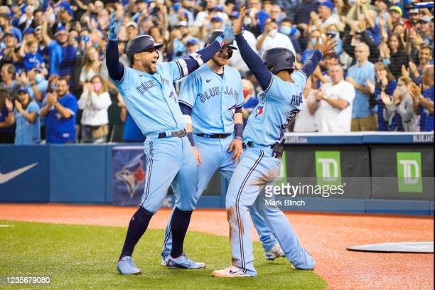 George Springer of the Toronto Blue Jays celebrates his grand slam with Teoscar Hernandez and Danny Jansen in the third inning during their MLB game...