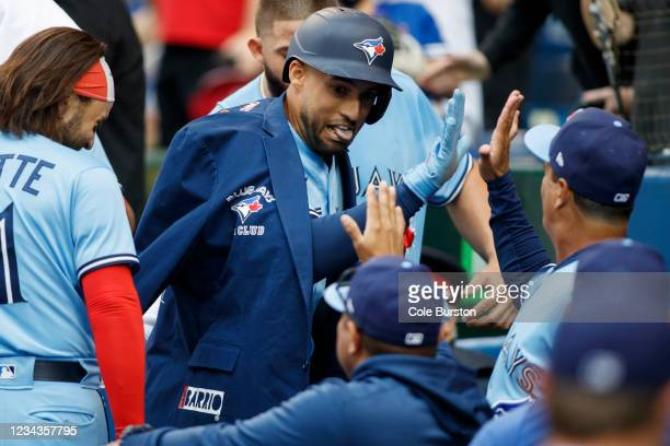 George Springer of the Toronto Blue Jays celebrates in the dugout with teammates after hitting a home run in the first inning during their MLB game...