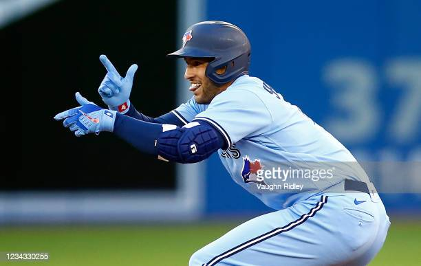 George Springer of the Toronto Blue Jays reacts after hitting a double in the second inning during a MLB game against the Kansas City Royals at...