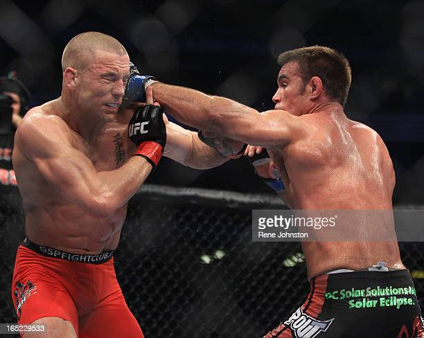 George St Pierre of Montreal takes a punch from Jake Sheilds of California at UFC 129