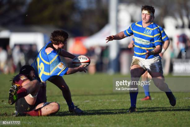 George Stratton of Lincoln offloads the ball to Anty Burnett of Lincoln during the Canterbury Metro Trophy Final match between Lincoln University and...