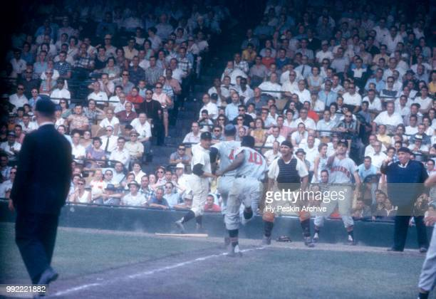 George Strickland and Vic Power of the Cleveland Indians score as catcher Lou Berberet of the Detroit Tigers looks on during an MLB game on July 4...