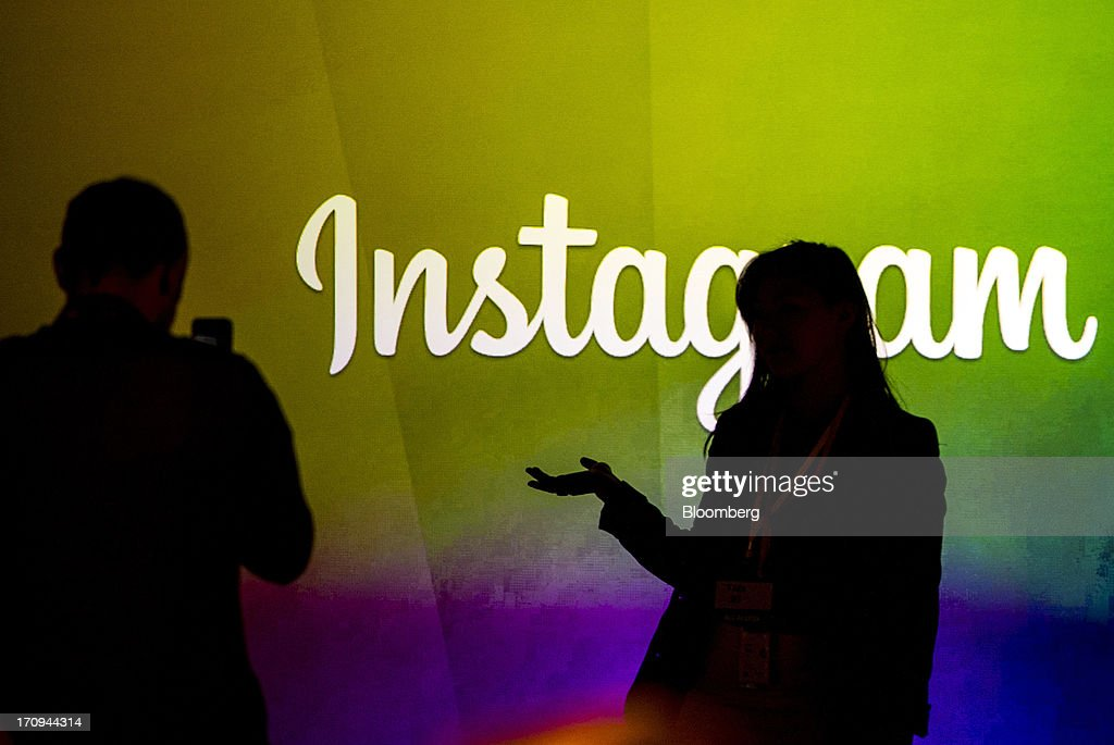 George Sylvain, left, takes a photograph of Tara Shi while standing in front of the Instagram Inc. logo during an event at Facebook Inc. headquarters in Menlo Park, California, U.S., on Thursday, June 20, 2013. Facebook Inc., operator of the largest social network, plans to unveil video-sharing tools, bringing its Instagram into closer competition with Twitter Inc., a person with knowledge of the matter said. Photographer: David Paul Morris/Bloomberg via Getty Images
