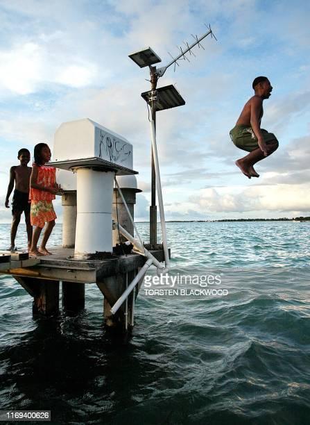 George Teleke uses the University of Hawaii's broken tidal gauge as a diving board on Funafuti Atoll, 22 February 2004, the 2.8 square kilometre home...