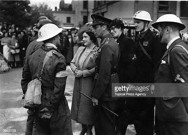 George VI King of Great Britain and Queen Elizabeth talking to workmen employed to demolish buildings damaged in an air raid on west London