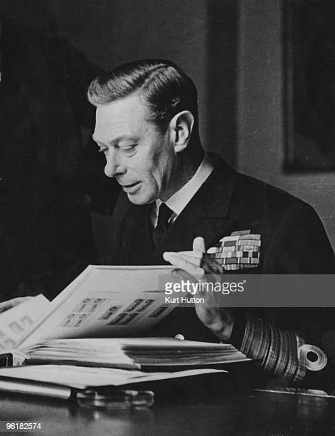 George VI, , King of Great Britain, peruses his stamp collection, December 1944. Original publication: Picture Post - 1860 - The King And His Stamps...