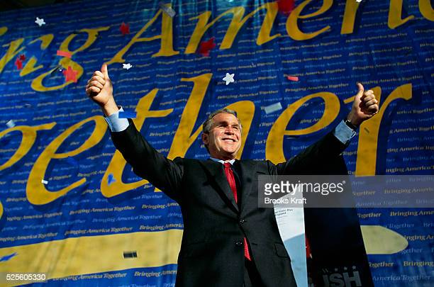 "George W. Bush attends a presidential campaign rally and gives two thumbs up in front of a banner that reads, ""Bringing America Together."" Bush won..."