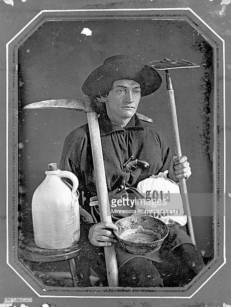 George W Northrup a soldier and gold miner sits with his mining tools and a bag of gold in Minnesota
