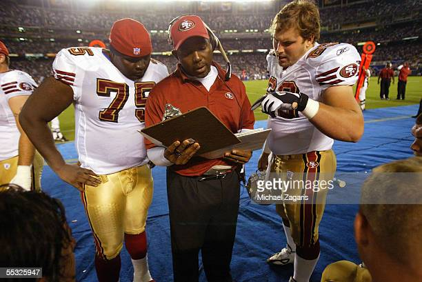 George Warhop meets with Jonas Jennings and Norm Katnik of the San Francisco 49ers during the preseason game against the San Diego Chargers on...