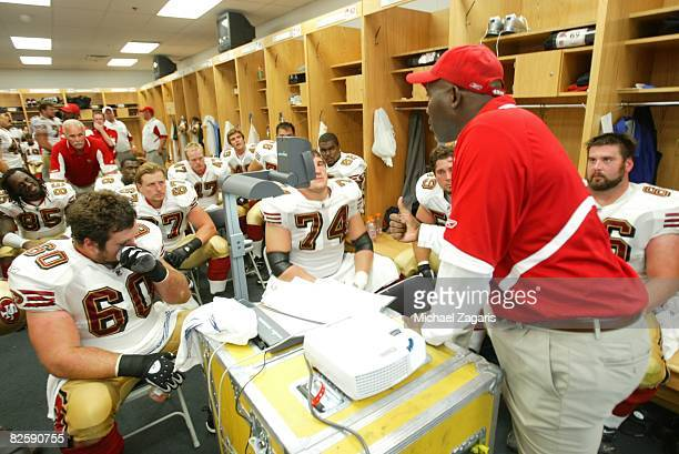George Warhop of the San Francisco 49ers addresses the offensive line in the locker room at halftime during the NFL game against the Chicago Bears at...
