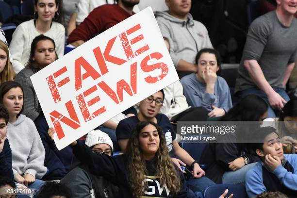 George Washington Colonials fans holds up a fake news sign during a college basketball game against the George Washington Colonials at the Capital...