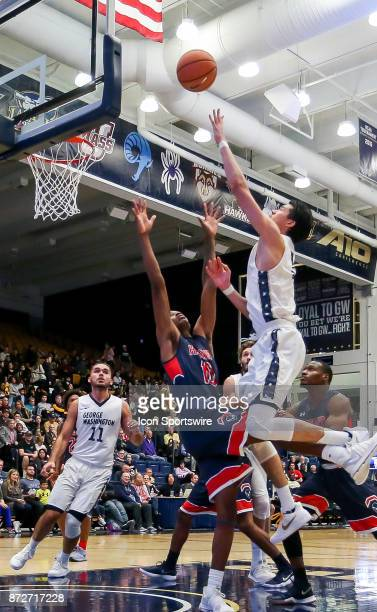 George Washington Colonials guard Yuta Watanabe shoots over Howard Bison forward Zion Cousins during a men's college basketball game between the...