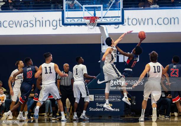 George Washington Colonials guard Yuta Watanabe tries to stop a shot by Howard Bison forward Charles Williams during a men's college basketball game...
