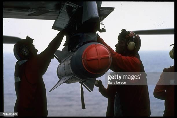 USS George Washington crewmen loading bomb onto warplane abd carrier off coast of Kuwait