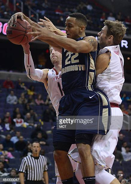 George Washington guard Joe McDonald pulls in a rebound against Maryland forward Evan Smotrycz and Maryland guard Jake Layman in the second half of...