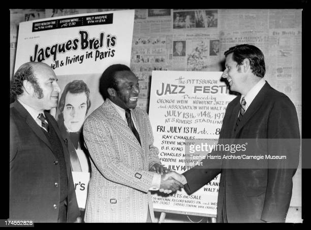 George Wein and Walt Harper shaking hands with Pittsburgh Mayor Pete Flaherty in front of broadside for Pittsburgh Jazz Festival and Jacques Brel in...