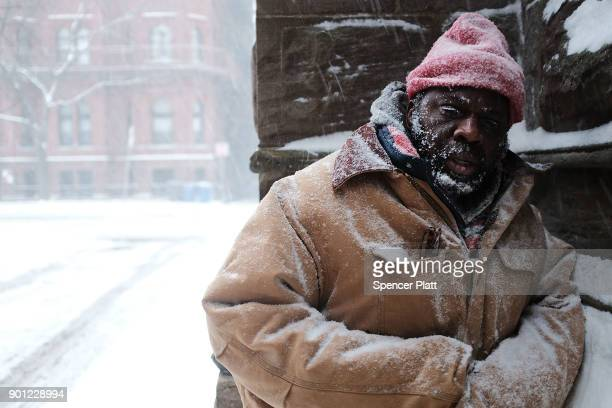 George who is homeless pauses in a church alcove on the streets of Boston as snow falls from a massive winter storm on January 4 2018 in Boston...