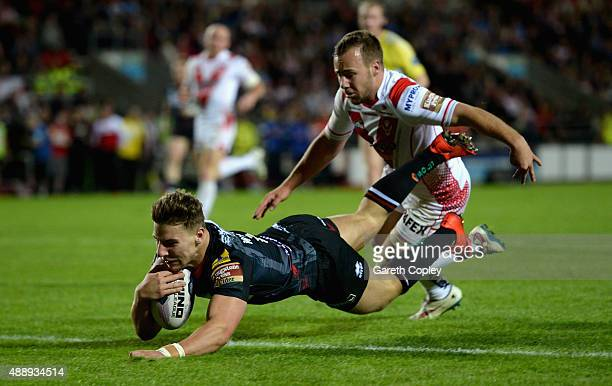 George Williams of Wigan Warriors scores a second half try past Adam Quinlan of St Helens during the First Utility Super League match between St...