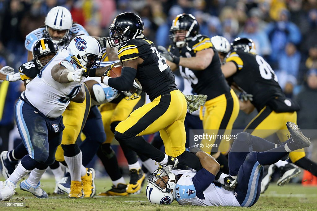 George Wilson #21 of the Tennessee Titans is stepped on as he attempts to tackle Le'Veon Bell #26 of the Pittsburgh Steelers in the second quarter at LP Field on November 17, 2014 in Nashville, Tennessee.