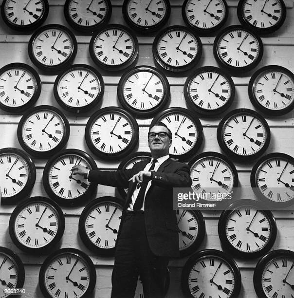 George Wren standing in front of a collection of clocks used for timing Civil Service exams