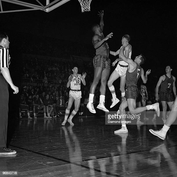George Yardley of the Fort Wayne Zollner Pistons fakes a shot and passes the ball to Jim Holstein as Maurice Stokes of the Rochester Royals tries to...