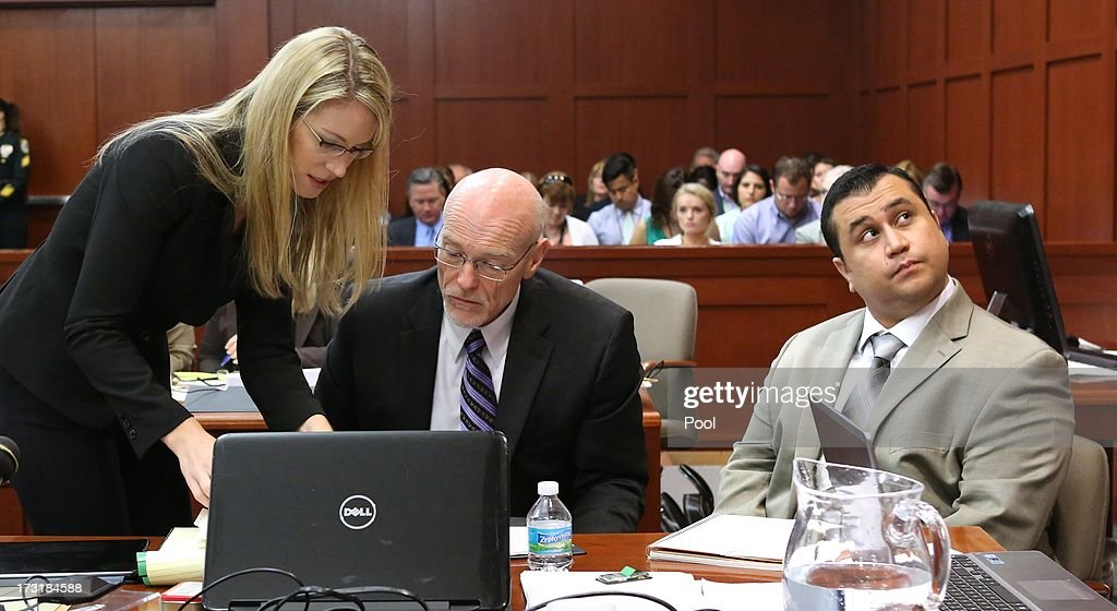 George Zimmerman looks up at a projection screen as defense counsel Don West talks to an assistant during the trial in Seminole circuit court, July 9, 2013 in Sanford, Florida. Zimmerman has been charged with second-degree murder for the 2012 shooting death of Trayvon Martin.
